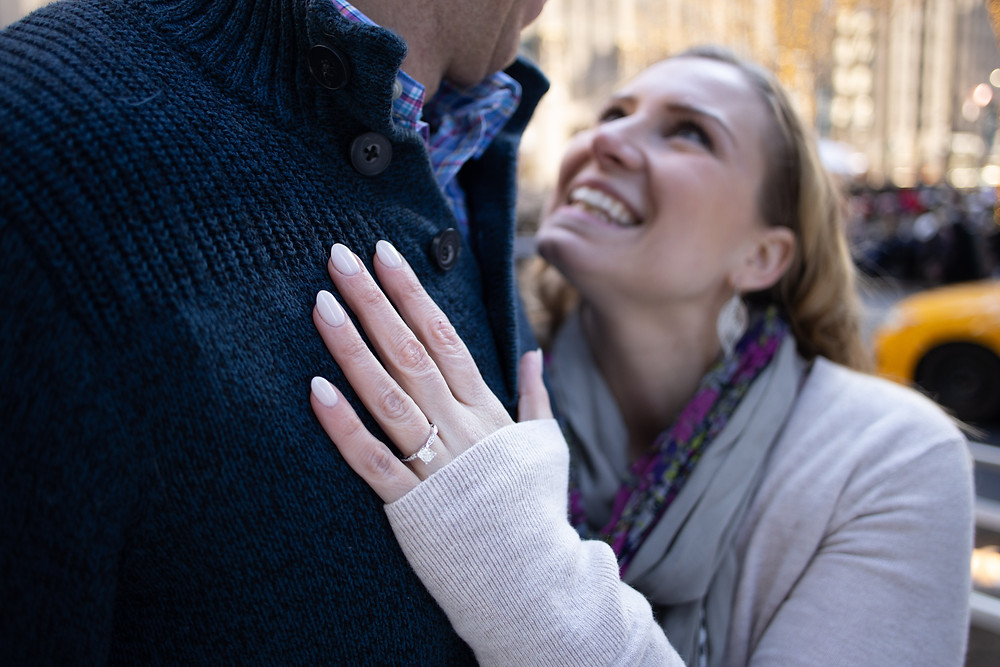 woman looking up at fiance during engagement session in new york city featuring the ring