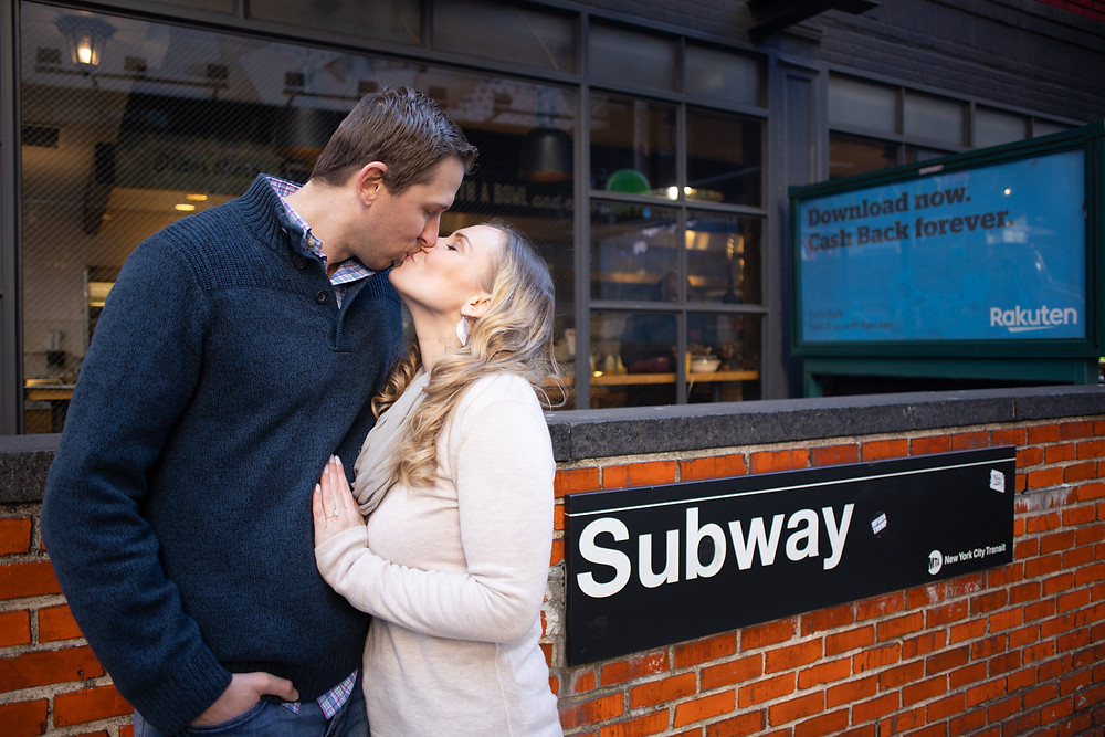 woman kissing her fiance in new york city by the subway