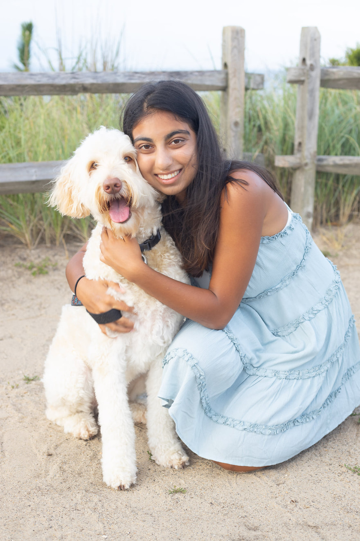dog and girl posing for camera at beach