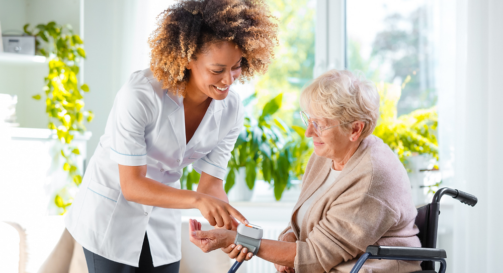 Self employed Live-in Carer helping measure an elderly woman's blood pressure