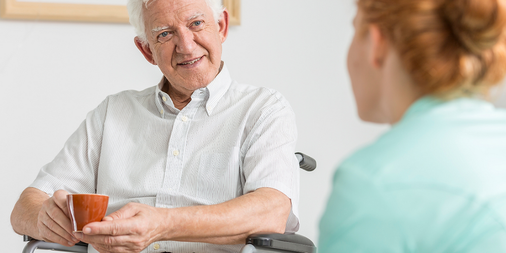Elderly man with Multiple Sclerosis talking to his Live-in Carer