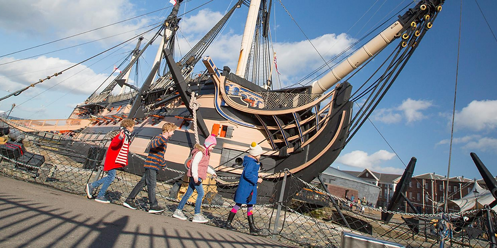 Children walking next to a boat at the Historic Dockyard in Portsmouth Hampshire