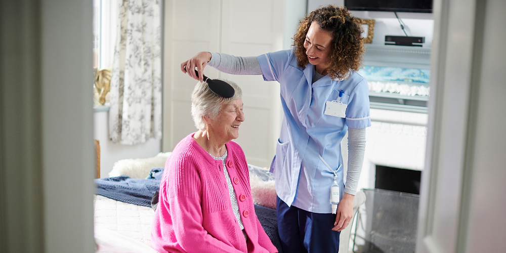 Elderly woman in pink jumper having her hair brushed by a live-in carer