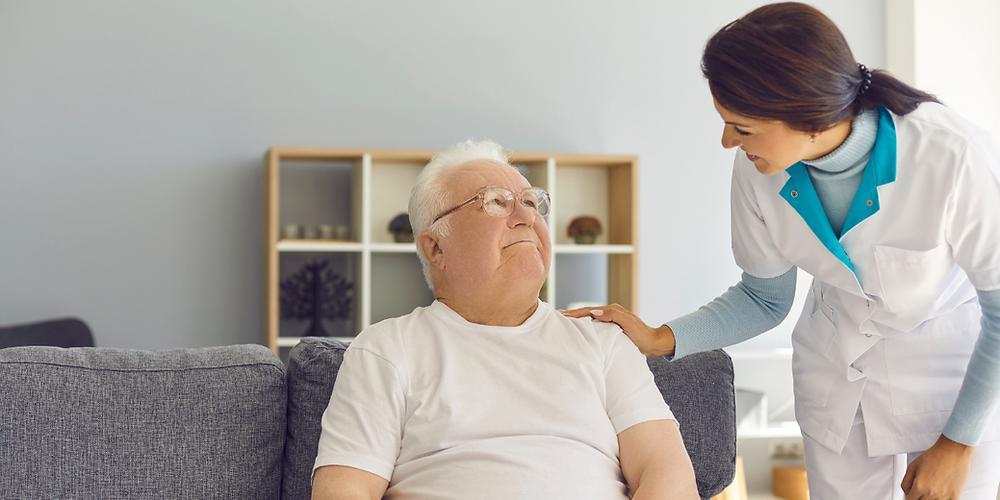 Elderly man wearing glasses with live-in carer placing hand on his shoulder