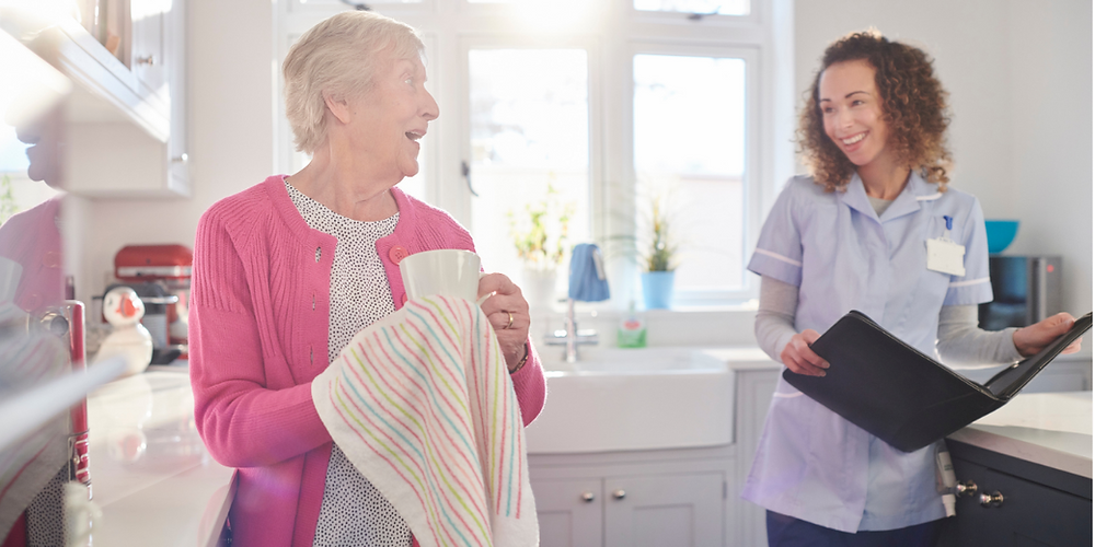 Elderly woman wearing a pink jumper chatting with a live-in carer in her kitchen