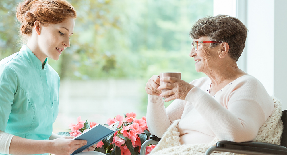 Live-in carer reading a book to an elderly woman