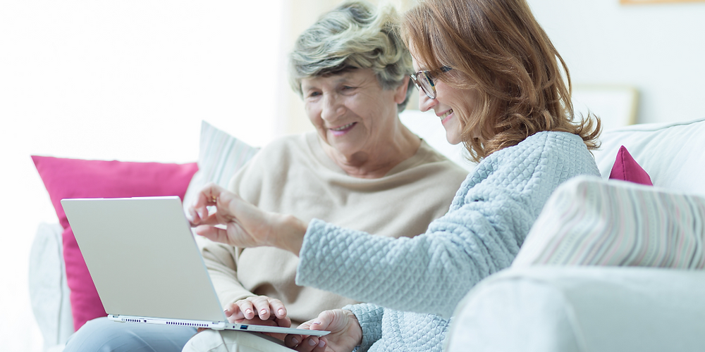 Elderly woman and live-in carer looking at a laptop screen