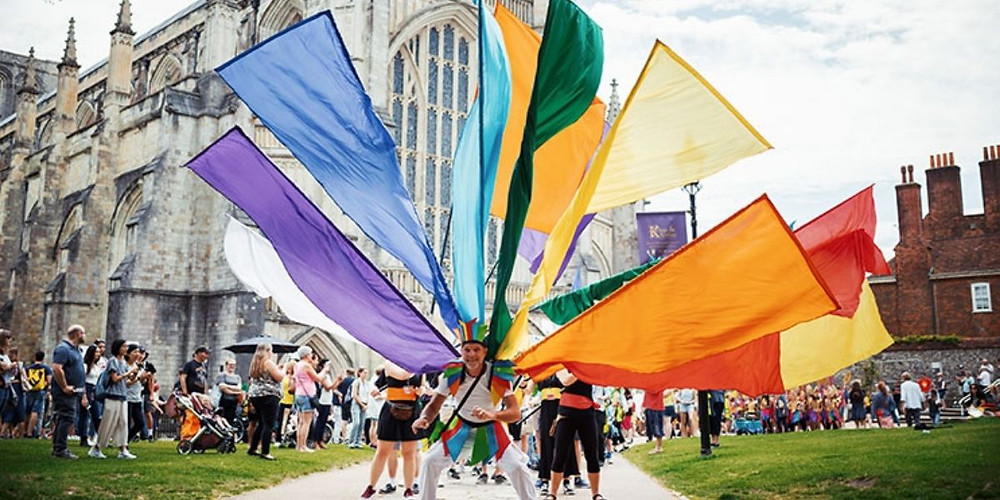 Man with multicoloured flags in front of Winchester Cathedral at Winchester Hat Fair in Hampshire