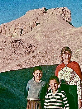 Mary Dana Marks with boys, Kerman, Iran. Ruins of Qaleh Dokhtar (girls' fortress in background.