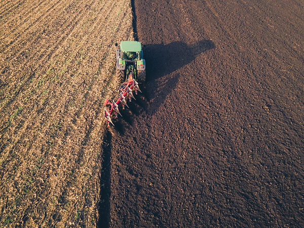 aerial-photo-of-a-tractor-ploughing-a-fi