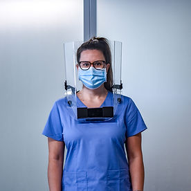 Female First responder wearing the Ultralite Total Comfort Face Shield, disposable mask and blue scrubs