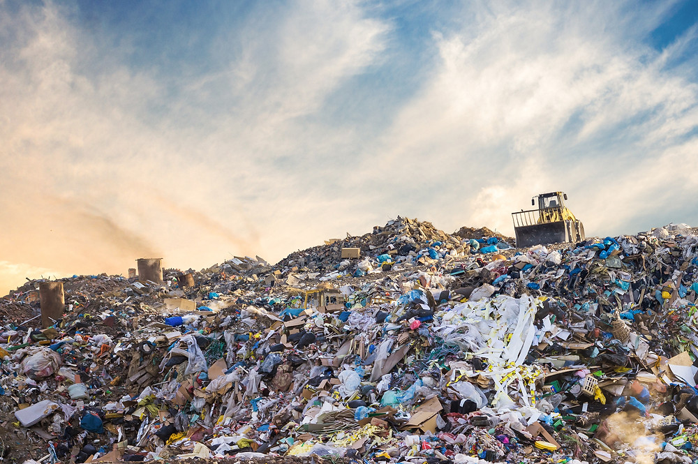 Yellow Bulldozer on top of a landfill, piled high with harmful waste and trash