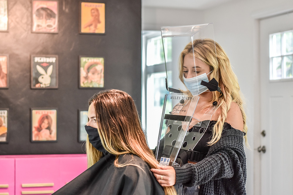 Blonde hair stylist cutting woman's hair with face shield and mask on