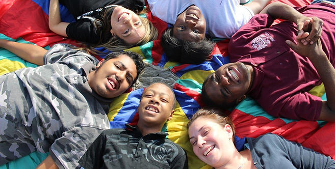 Smiling children laying on parachute outside