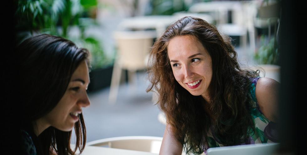 two-talking-women-while-using-laptop-131