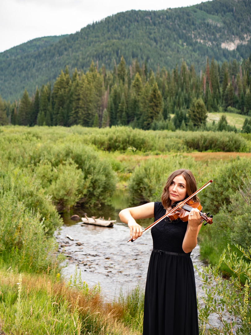 First String Violinist, a wedding musician in Utah, plays the violin by a stream.