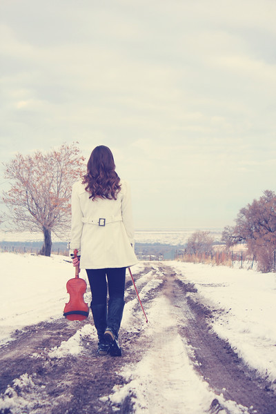 Event violinist Jessica McAllister walks down a snowy Utah road with her violin.