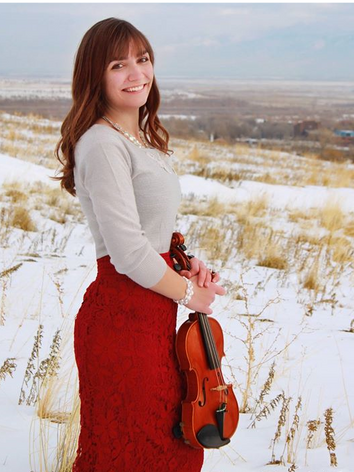 Jessica McAllister holds her violin in a winter field in Utah.