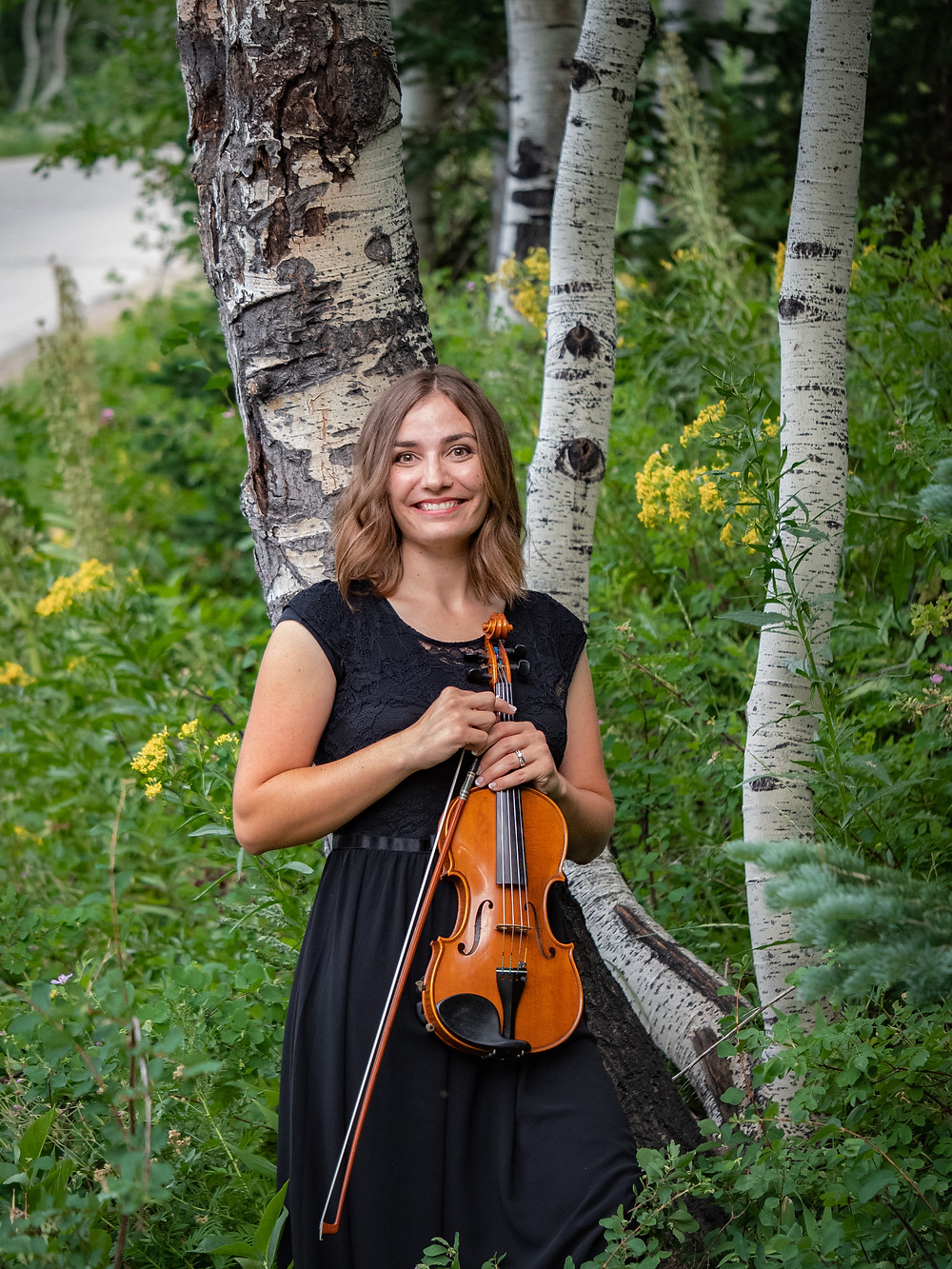 Jessica McAllister: violinist in Utah stands by tree in mountains