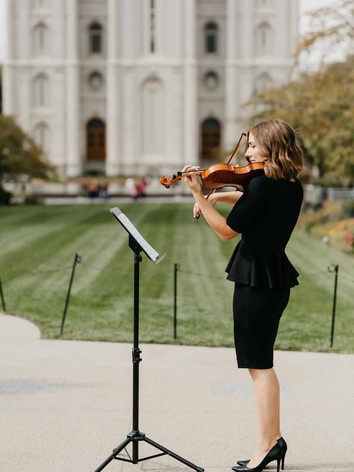 Jessica McAllister performs the violin for a wedding in front of the Salt Lake City Utah LDS temple.