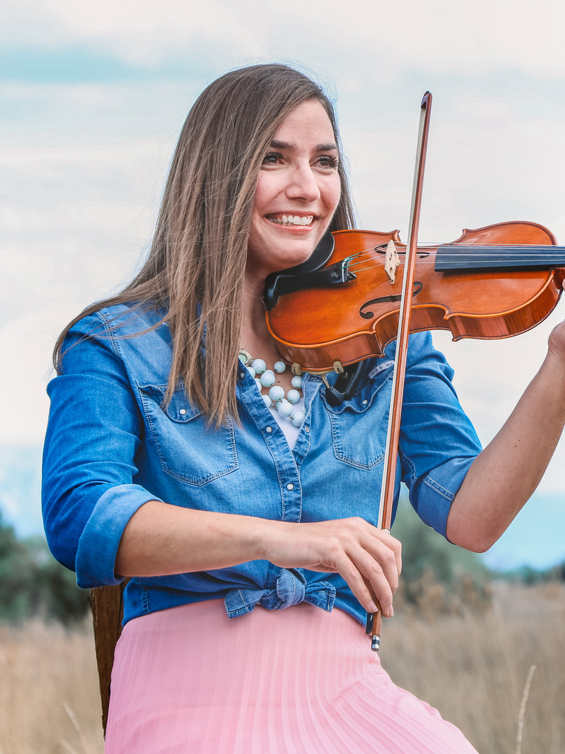 Violinist Jessica McAllister, First String Violinist, sits on a fence in Utah while playing the violin.