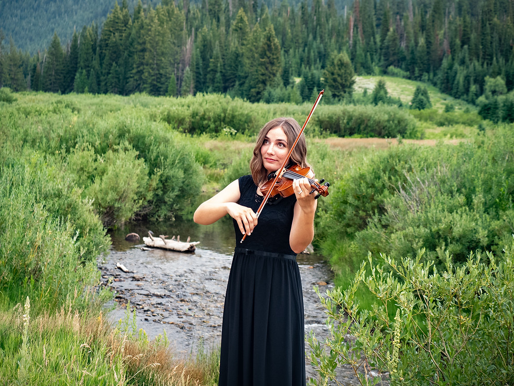 beautiful event violinist, Jessica McAllister plays by a river in Utah