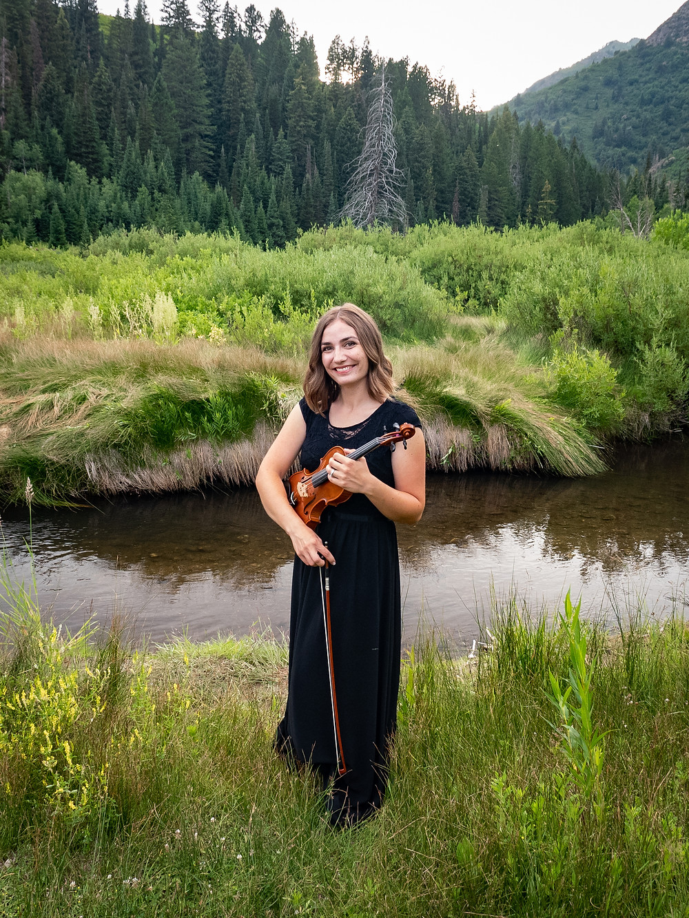 First String Violinist holds violin by a river in Utah