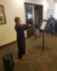 Jessica McAlliste's young male violin student playing a recital