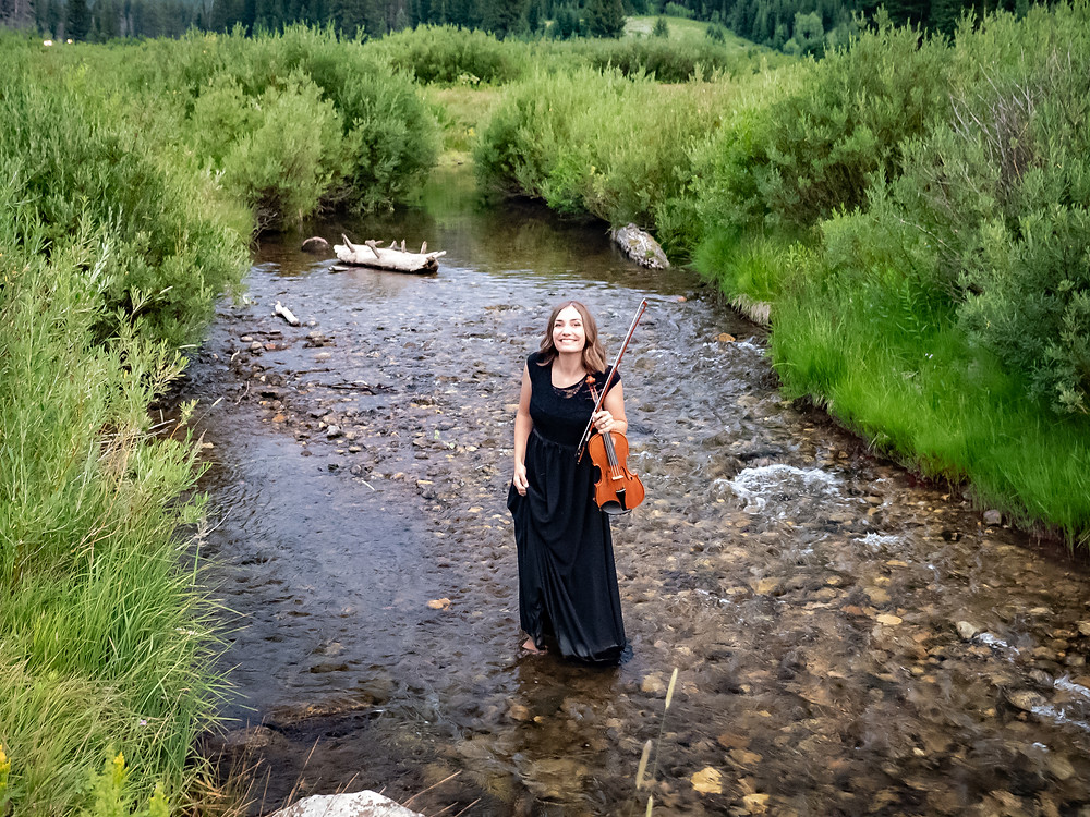 event musician in Utah stands in a cold river with violin