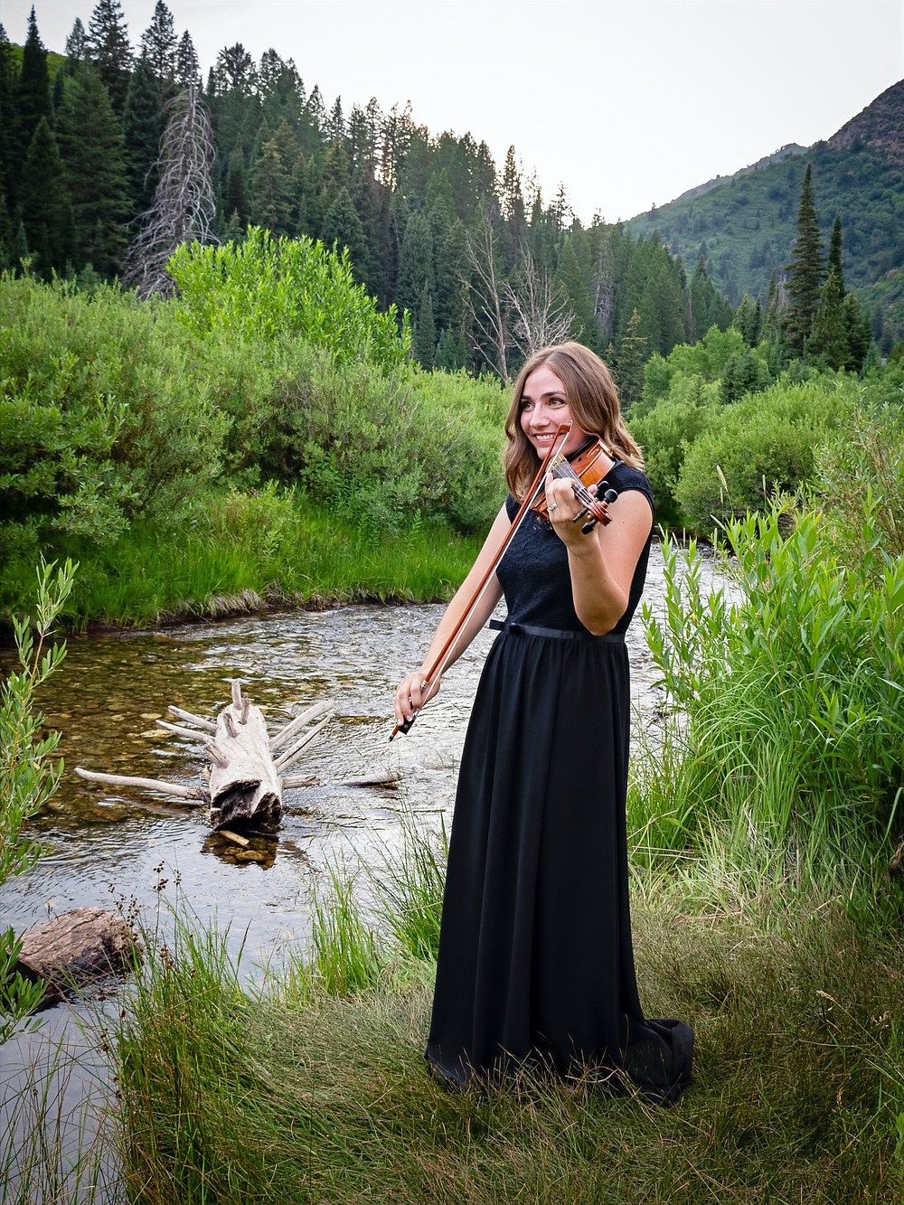 First String Violinist playing the violin by a beautiful river in Utah