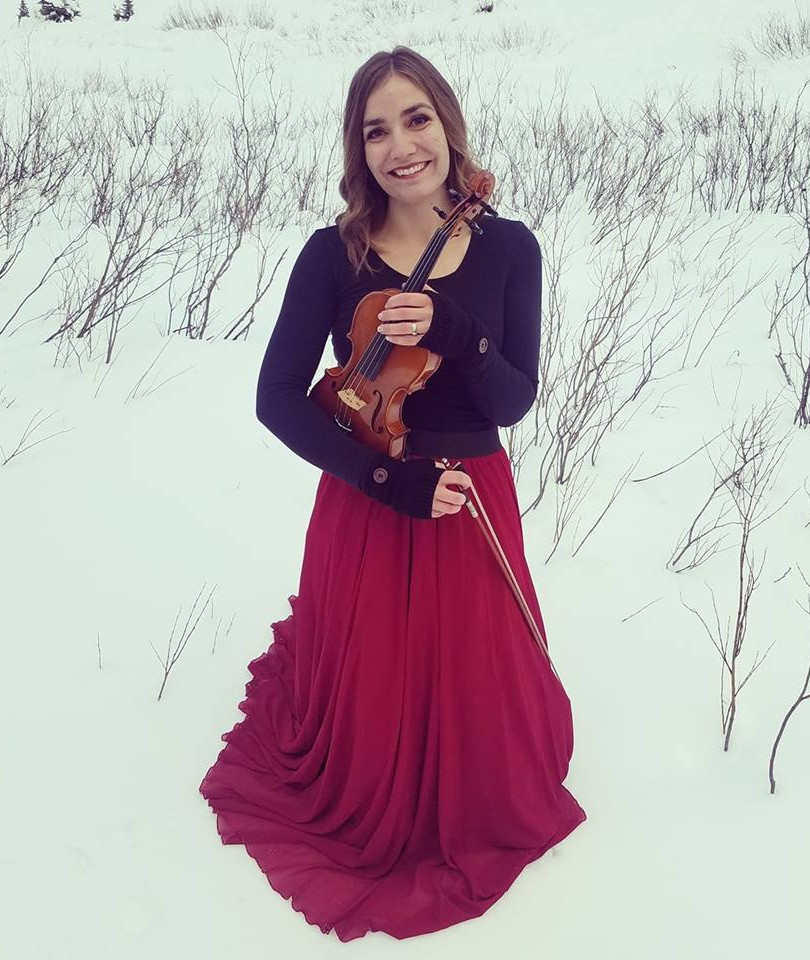 Utah Violinist Jessica McAllister smiles in knee deep snow in the mountains.