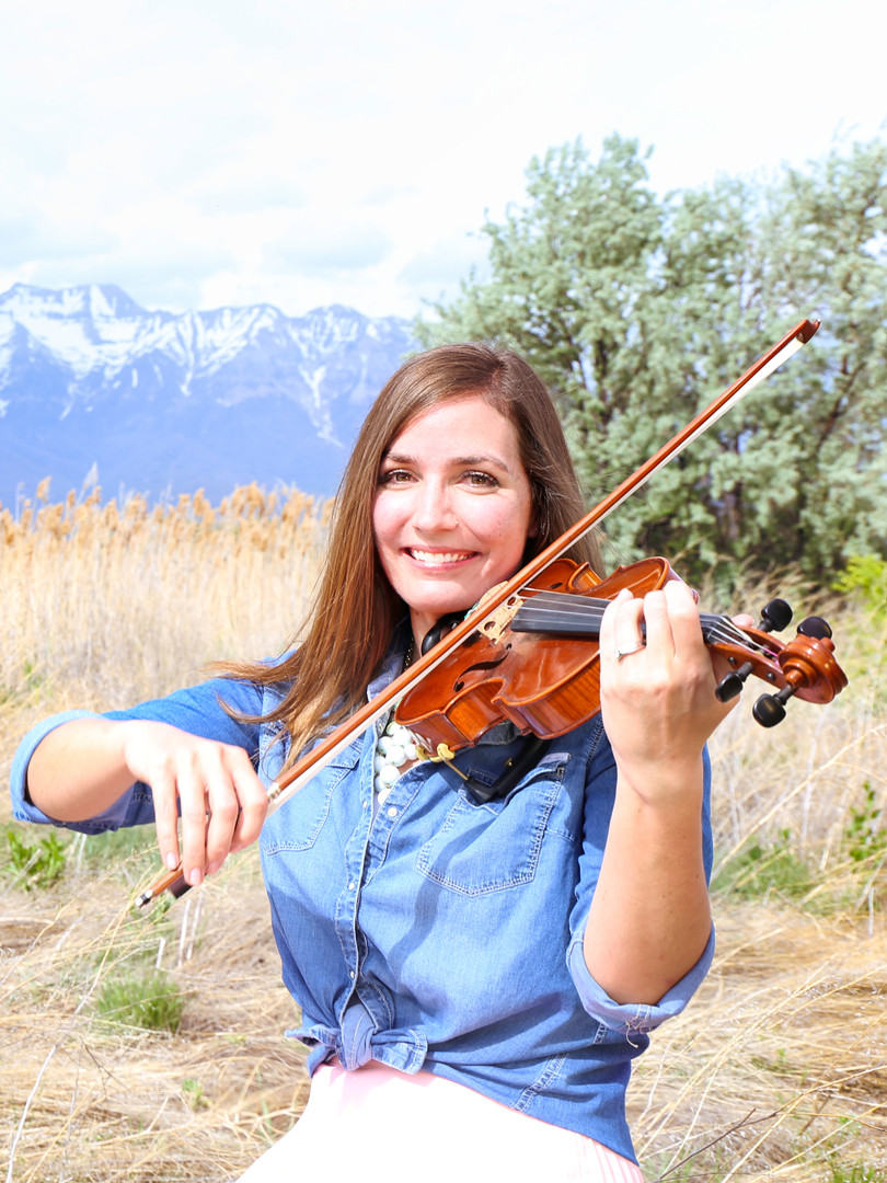 Jessica McAllister, a solo violinist for hire for weddings plays the violin in a field in Utah.