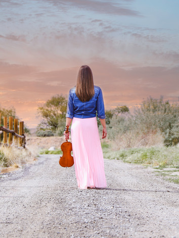 First String Violinist, Jessica McAllister, walks down a dirt road at sunset carrying her violin.