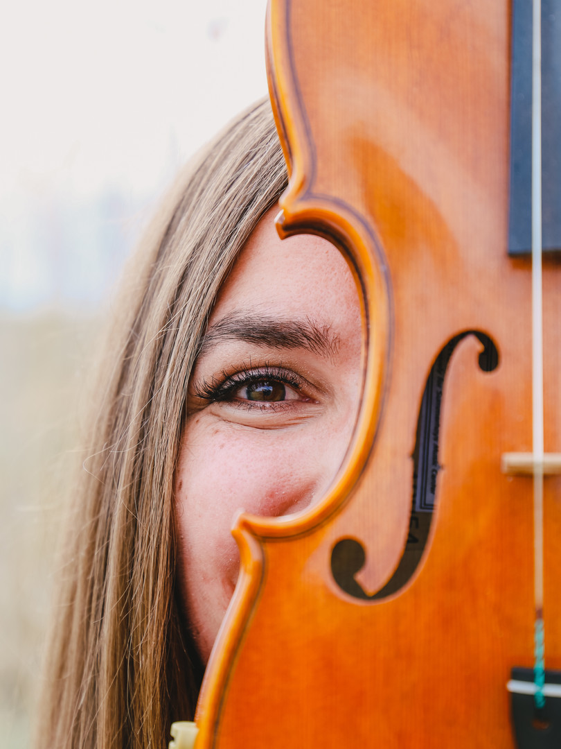 First String Violinist holds a violin up to her face.