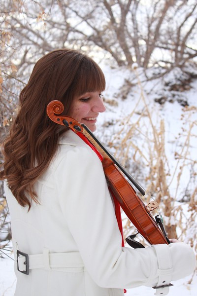 First String Violinist, Jessica McAllister smiles at her violin in the Utah snow.