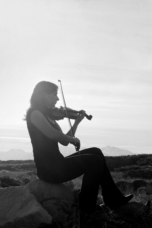 black and white violinist plays on rocks in Utah