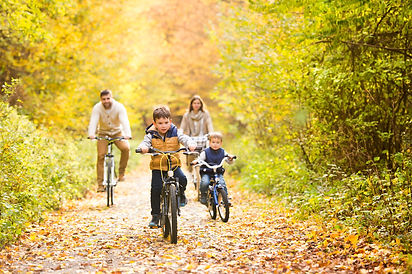 Young family in warm clothes cycling in