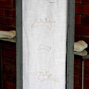 Gold thread footprint embroidery on linen.