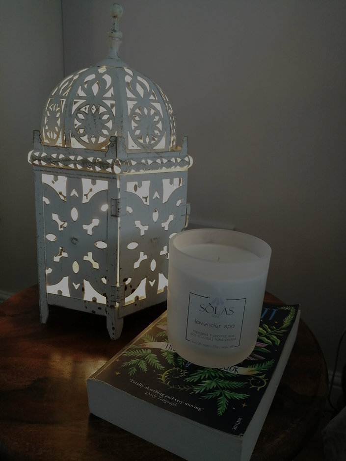 SOLAS candle burning next to a moorish inspired cutout metalwork lamp, placed ontop of a botanical b
