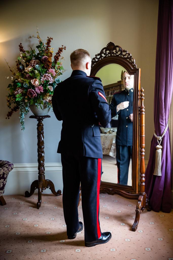 Groom looking into a mirror