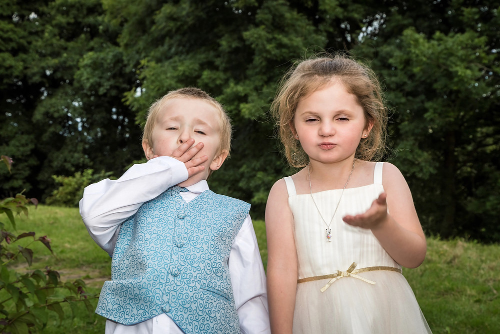 Wedding kids blowing kisses to the photographer.
