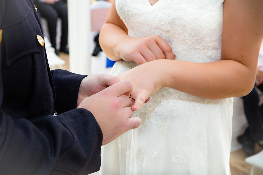 Groom placing a ring on the brides finger