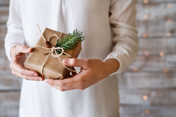 young-woman-holding-wrapped-christmas-pr