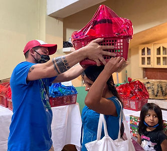 Kevin helps set Christmas food basket on local woman's head.