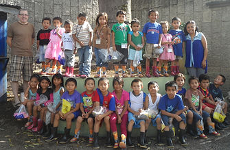 Some of the children from Santa Fe pose with Pat and Yesenia in their new rain boots.
