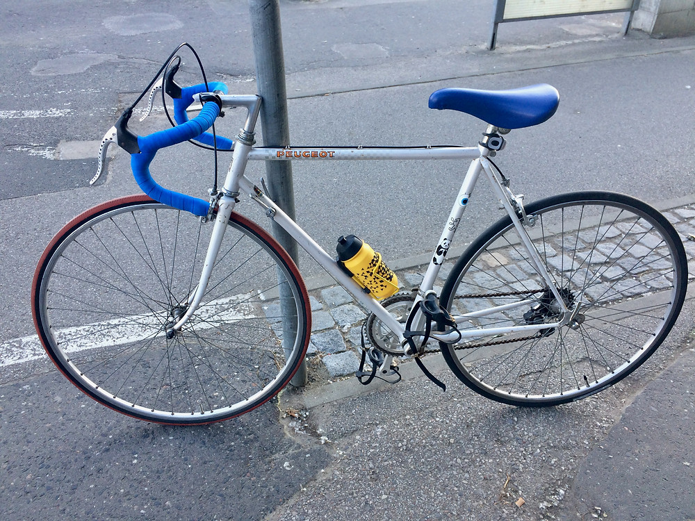 Vintage bike - Peugeot - parked alongside of the road