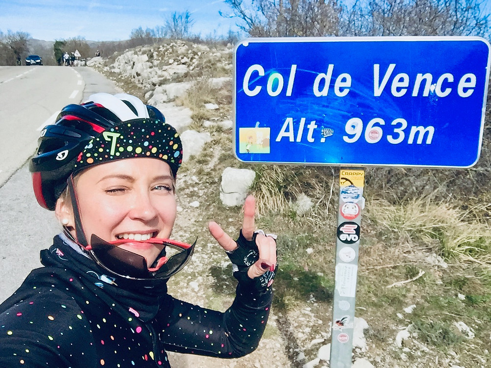 Aleks posing at the front of Col de Vence signage