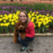 Shannon Reyenga is shown with her goldendoodle Colfax. She has glasses and blonde hair. She is smiling because she is in a tulip field.