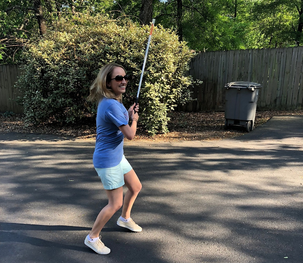 "Image description: A photo of Shannon on her driveway. She is wearing green shorts, a blue shirt and sunglasses."" Her hair is down and she is smiling and swinging her cane up in the air.."