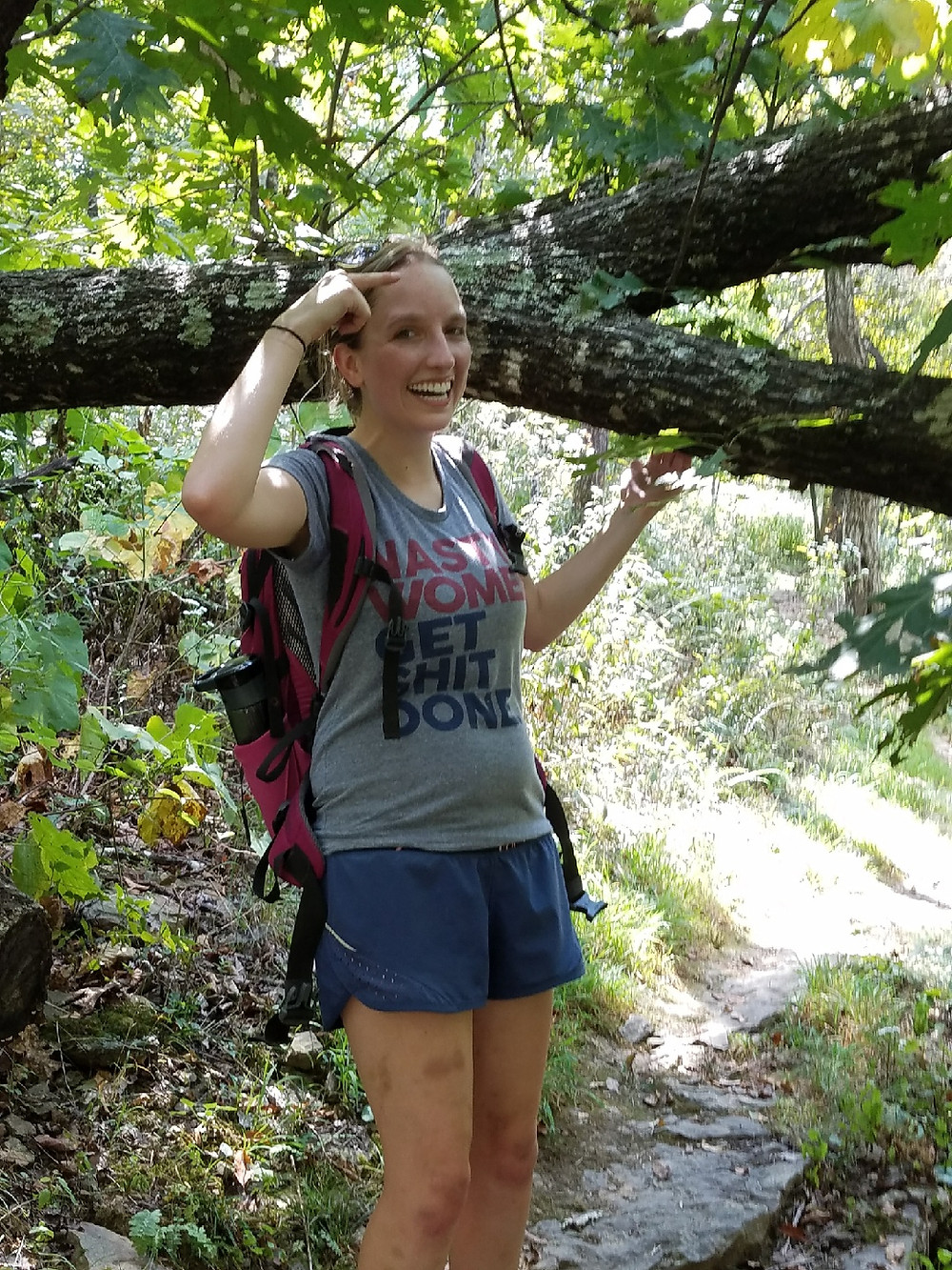 Shannon poses in front of a large tree branch next to her. She is smiling and pointing at her head. She is dressed in hiking clothing - a t--shirt, shorts and a camelback backpack.